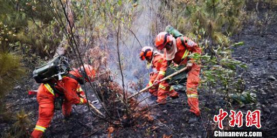 消防员正在清理火场。 王绍刚 摄